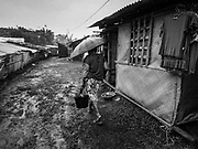 26 JANUARY 2018 - SANTO DOMINGO, ALBAY, PHILIPPINES: A woman walks between thatched huts and tents for evacuees from the Mayon Volcano at Barangay Lidong shelter. The shelter is in school and all of the classrooms are already being used to house evacuees. Recent arrivals are living in tents and huts on the school grounds. The volcano was relatively quiet Friday, but the number of evacuees swelled to nearly 80,000 as people left the side of  the volcano in search of safety. There are nearly 12,000 evacuees in Santo Domingo, one of the communities most impacted by the volcano. The number of evacuees is impacting the availability of shelter space. Many people in Santo Domingo, on the north side of the volcano, are sleeping in huts made from bamboo and plastic sheeting. The Philippines is now preparing to house the volcano evacuees for up to three months.        PHOTO BY JACK KURTZ