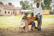 View of kids sitting at desk and writing while teacher is explaining, The Musoto Christian School, Uganda