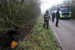 Denham, UK. 6 February, 2020. Extinction Rebellion activists pick up litter whilst fellow environmental activists block a security vehicle and truck delivering fencing and other supplies to be used for works associated with the HS2 high-speed rail link close to the river Colne at Denham Ford. Works planned in the immediate vicinity include the felling of trees and the construction of a Bailey bridge, compounds and fencing, some of which in a wetland nature reserve forming part of a Site of Metropolitan Importance for Nature Conservation (SMI).