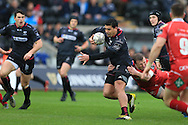Josh Matavesi of the Ospreys © looks to break free of his tackler. Guinness Pro12 rugby match, Ospreys v Scarlets at the Liberty Stadium in Swansea, South Wales on Saturday 26th March 2016.<br /> pic by  Andrew Orchard, Andrew Orchard sports photography.