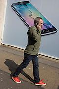 Phone user walks past Samsung shop window ad for new S6 model.