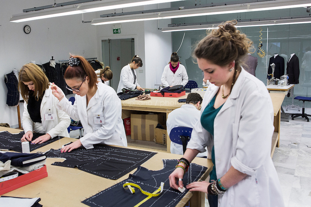 ARZANO, ITALY - 16 January 2014: Students work on a blazer at the Kiton School of High Tailoring inside the Kiton factory in Arzano, Italy, on January 16th 2014.