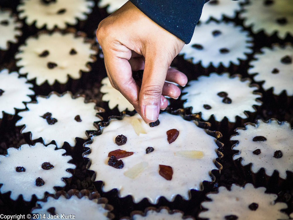 """28 OCTOBER 2014 - BANGKOK, THAILAND: A worker drops raisins on a cake at the Pajonglak Maneeprasit Bakery in Bangkok. The cakes are called """"Kanom Farang Kudeejeen"""" or """"Chinese Monk Candy."""" The tradition of baking the cakes, about the size of a cupcake or muffin, started in Siam (now Thailand) in the 17th century AD when Portuguese Catholic priests accompanied Portuguese soldiers who assisted the Siamese in their wars with Burma. Several hundred Siamese (Thai) Buddhists converted to Catholicism and started baking the cakes. When the Siamese Empire in Ayutthaya was sacked by the Burmese the Portuguese and Thai Catholics fled to Thonburi, in what is now Bangkok. The Portuguese established a Catholic church near the new Siamese capital. Now just three families bake the cakes, using a recipe that is 400 years old and contains eggs, wheat flour, sugar, water and raisins. The same family has been baking the cakes at the Pajonglak Maneeprasit Bakery, near Santa Cruz Church, for more than 245 years. There are still a large number of Thai Catholics living in the neighborhood around the church.   PHOTO BY JACK KURTZ"""