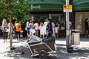 A male street cleaner collecting rubbish and litter outside the world famous and iconic Harrods department store in Knightsbridge, London, United Kingdom.  Groups of tourists are in the background looking at the shop's window displays being guided around London by Embassy Staff.