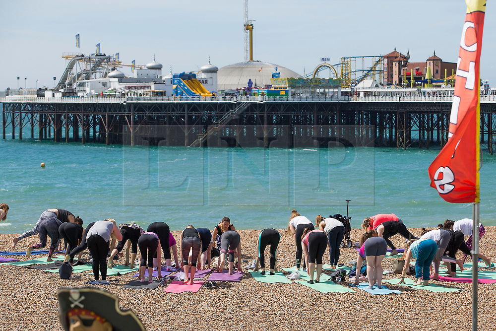 © Licensed to London News Pictures. 03/06/2017. Brighton, UK. Members of the public take their yoga class in the sunshine on the beach in Brighton and Hove. Photo credit: Hugo Michiels/LNP