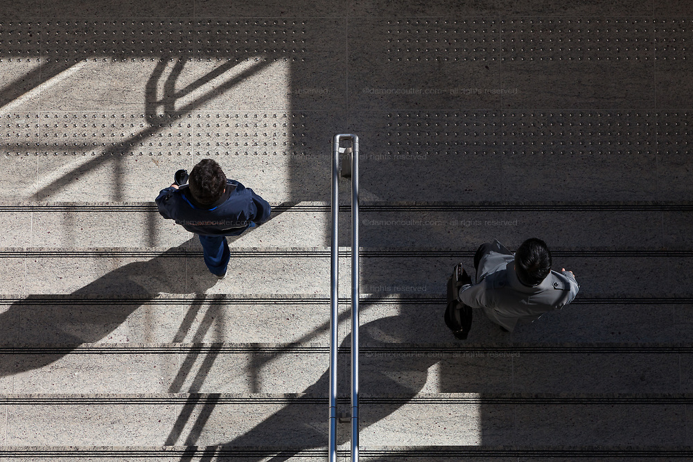 A salarymen and another man going  down some steps at Tokyo Station, Tokyo, Japan. Friday, January 10th 2014