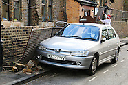 Car damaged after storm falling wall