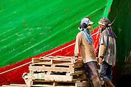 Dock workers taking a break beside a ship docked at Sunda Kelapa (the old port) in Jakarta, Indonesia.