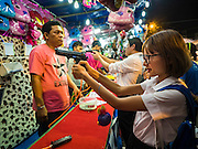 24 NOVEMBER 2015 - BANGKOK, THAILAND:  A young woman shoots a bb gun at an arcade shooting gallery at the Wat Saket temple fair. Wat Saket is on a man-made hill in the historic section of Bangkok. The temple has golden spire that is 260 feet high which was the highest point in Bangkok for more than 100 years. The temple construction began in the 1800s in the reign of King Rama III and was completed in the reign of King Rama IV. The annual temple fair is held on the 12th lunar month, for nine days around the November full moon. During the fair a red cloth (reminiscent of a monk's robe) is placed around the Golden Mount while the temple grounds hosts Thai traditional theatre, food stalls and traditional shows.       PHOTO BY JACK KURTZ