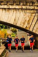 Group of men jogging along the banks of the River Seine, near Pont de la Concorde, Paris, France.