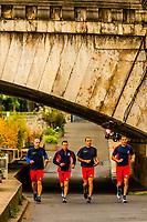 Group of men jogging along the banks of the River Seine, near Pont de la Concorde, Paris, France.