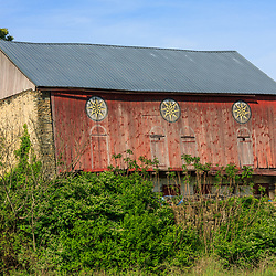 Hamburg, PA, USA- May 12, 2012: An older Pennsylvania Dutch red barn with Hex signs in disrepair in Berks County, PA.