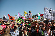 Glastonbury Festival on June 27th 2019 in Glastonbury, Somerset, United Kingdom. A joint Extinction Rebellion and Greenpeace rally and procession on the Park Stage going to the stones in the Sacred Space. The festival has been going for decades and this year the sun is beating down promising a dry weekend.