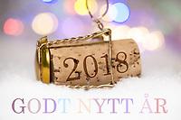Nyttårshilsen i form av Champagne-kork med innpreget årstall 2018 og pastell «Godt nytt år»  tekst. Det er tillatt å skrive både «Godt nytt år» og «Godt nyttår». Hva man velger blir personlig preferanse.