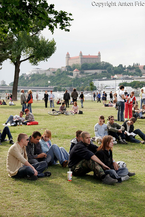 People picnicking at the right bank of river Danube (Petrzalka) in Bratislava, Slovakia  with Bratislava castle in the back.