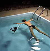 Woman floating in pool facedown.