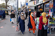 As Londoners from the mainly Bangladeshi Asian community await the second coronavirus national lockdown it's business as usual at Whitechapel Market with people out and about, some wearing face masks and some not, on what will be the few days of normality before a month-long total lockdown in the UK on 2nd November 2020 in London, United Kingdom. The three tier system in the UK has not worked sufficiently, to suppress the virus, and there have have been calls by politicians for a 'circuit breaker' complete lockdown to be announced to help the growing spread of the Covid-19.