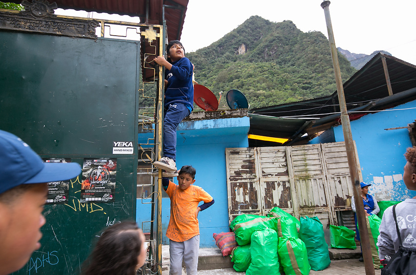 Bryan Carson, 15, far left, and Micah Walthall, 14, far right, walk by local children playing outside of Machu Picchu.