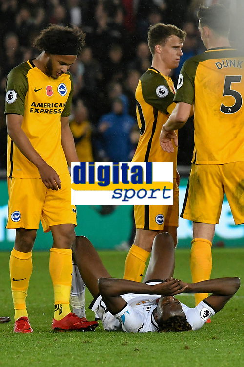 Football - 2017 / 2018 Premier League - Swansea City vs. Brighton & Hove Albion<br /> <br /> Tammy Abraham of Swansea City lies on his back among the Brighton players after Swansea lose , at The Liberty Stadium.<br /> <br /> COLORSPORT/WINSTON BYNORTH