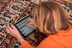 Relaxed senior woman working a digital tablet, Munich, Bavaria, Germany