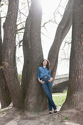 Mature woman leaning against tree in park, Bavaria, Germany