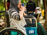 24 SEPTEMBER 2015 - BANGKOK, THAILAND: A woman kisses her Quran while praying in the cemetery at Haroon Mosque during the celebration of Eid al-Adha in Bangkok. Eid al-Adha is also called the Feast of Sacrifice, the Greater Eid or Baqar-Eid. It is the second of two religious holidays celebrated by Muslims worldwide each year. It honors the willingness of Abraham to sacrifice his son, as an act of submission to God's command. Goats, sheep and cows are sacrificed in a ritualistic manner after services in the mosque. The meat from the sacrificed animal is supposed to be divided into three parts. The family retains one third of the share; another third is given to relatives, friends and neighbors; and the remaining third is given to the poor and needy.     PHOTO BY JACK KURTZ