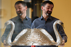 © Licensed to London News Pictures. 15/11/2016. Museum assistant holds a life-size swan centrepiece, made by Asprey & Co in 1985 for Rosalinde & Albert Gilbert. The piece is showing as part of the re-opening of the V & A's Rosalinde and Arthur Gilbert Galleries. London, UK. Photo credit: Ray Tang/LNP