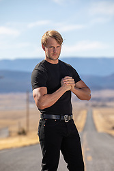rugged blond man on a long road in The Southwest
