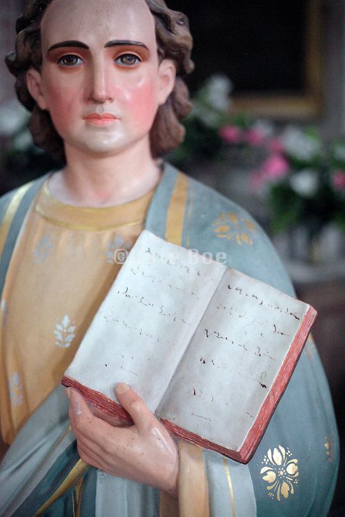 male person statue holding a book with handwritten text