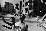 """Boys playing basketball in the ruins on the front line between Muslim East Mostar and Croat West Mostar. It was destroyed by systemic bombardment from Croat guns during the Croat Muslim War, when the Croats endeavored to """" cleanse"""" the town of non Croats. Mostar, Bosnia and Herzegovina."""