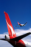 Qantas tailplane with plane passing.<br /> <br /> Larger JPEG + TIFF images available by contacting use through our contact page at : www.effectiveworkingimage.com