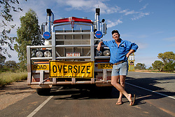 Driver of large Road Train heavy goods vehicle posing with his truck in outback Australia