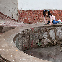 Girl playing at a water fountain in Aguas Calientes.