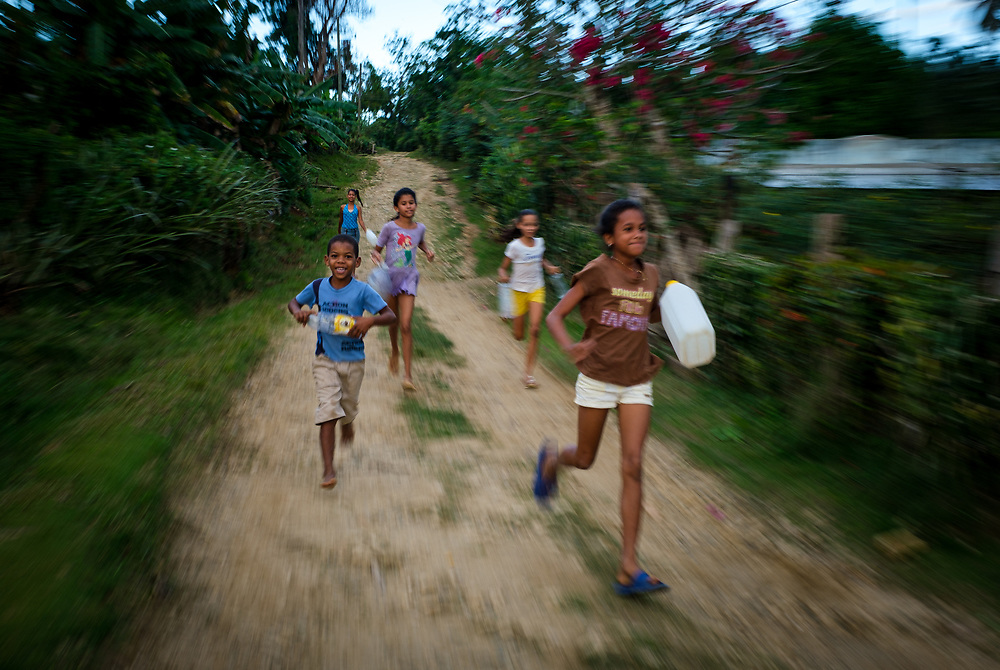 BARACOA, CUBA - CIRCA JANUARY 2020: Cuban kids running in the area around Bahia de Mata, a village close to Baracoa in Cuba.