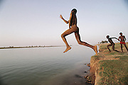 Boys run and leap into the Niger River in the late afternoon at the W. African village of Kouakourou, Mali. Material World Project.