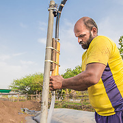 INDIVIDUAL(S) PHOTOGRAPHED: Prasad Tulpule. LOCATION: Ahirwade, Maharashtra, India. CAPTION: Prasad carries out a quick maintenance check on his recently installed biogas unit. This simple technology ferments organic waste and turns it into methane gas, which Prasad's family is then able to use instead of firewood for cooking. Now that Prasad has access to a reliable and clean source of energy, he hopes to use his biogas-fuelled cookstove to develop medicinal products to sell at the nearby market. Sistema Biobolsa, a social enterprise supported by Shell Foundation, has installed more than 4,000 biogas units to date, helping families across the globe to access affordable and renewable energy.
