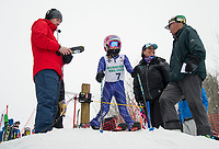 Ryan Waldron gets ready to start McKenna Howard's run as she waits in the start gate with coach Linda Otten during the first annual Candy Man Cup stubby slalom in memory of long time coach Dan Wheeler with Gunstock Ski Club.  (Karen Bobotas/for the Laconia Daily Sun)