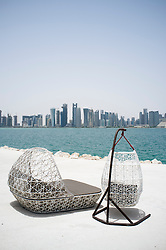Modern outdoor seating at waterfront cafe with view of skyline of Doha in Qatar
