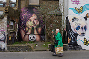 Local ladies walk past graffiti and urban artwork that features pandas and a child's face, on 20th January 2020, in Croydon, London, England.