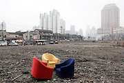 Sofas lay inside a demolished old neighborhood planned for redevelopment and temporarily serves as a parking lot in Shanghai, China on 04 February, 2009.  Large swaths of land in Shanghai has been cleared for new development in recent years, moving former residents out of the center of the city and driving up real estate prices in the process.