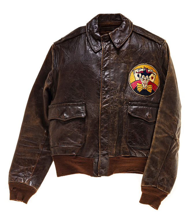 This type A-2 flight jacket was worn by a member of the 570th squadron, attached to the 390th Bomb Group. The 570th squadron insignia patch, a joker with 4 aces behind it, is attached to the front left of the jacket. There is no artwork on the back of the jacket, and no name plate on the front of it.