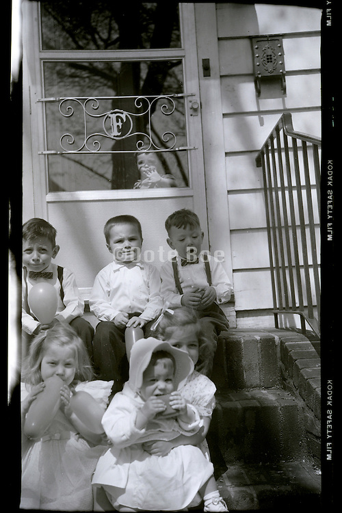 happy children moment sitting on stairs in front of door USA 1920s
