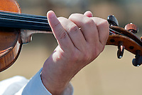 Close-up of hands playing violin outdoors during a concert.