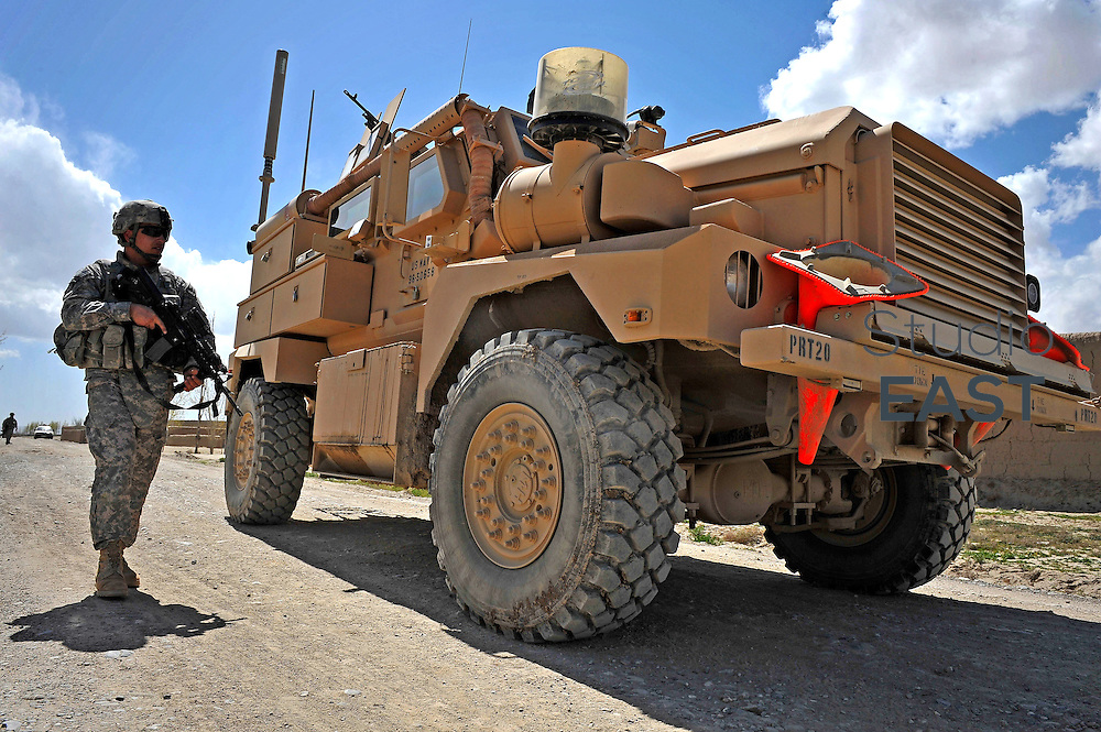 U.S. Private Malcolm of D Company, 2/130 Infantry, walks next to a Mine Resistant Ambush Protected Vehicle (MRAP) providing security for engineers of Provincial Reconstruction Team Paktika when they inspect a damaged culvert in a small village in Paktika Province, Afghanistan, on April 22, 2009. US forces in the region are sending out Provincial Reconstruction Teams in an effort to help rebuild or construct new infrastructures for the local inhabitants. Military involvement in development brought criticism from relief agencies that claimed it put them at risk by blurring the distinction between combatants and humanitarian workers. Photo by Simon Lim/Pictobank