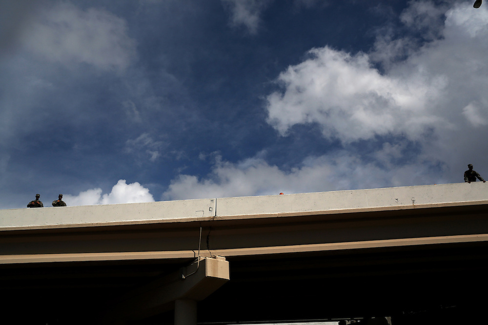 Security watches a protest march from an overpass during the 2012 Republican National Convention on August 28, 2012 in Tampa, Fla.