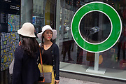 Two Asian girls check directions in central London near one of the green cirlces outside M&Ms Worlds Leicester Square store, on 31st July 2017, in London, England.