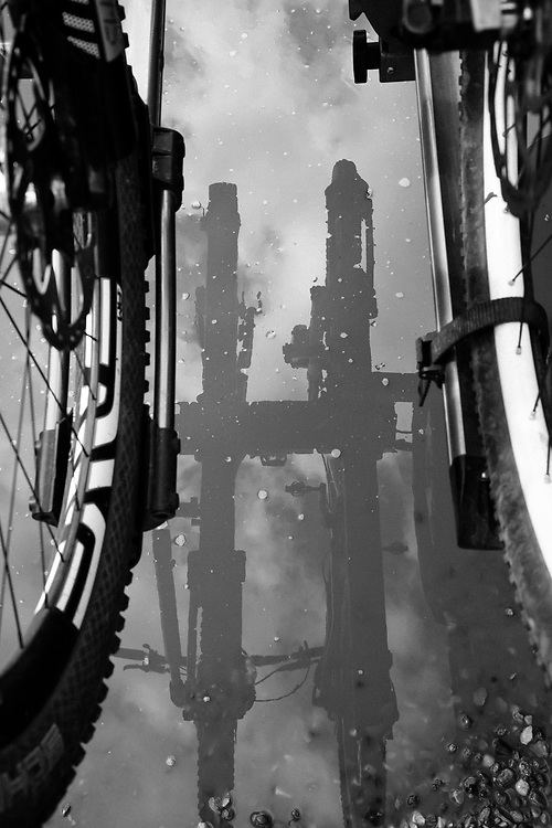 Bike wheels and clouds are reflected in a parking lot puddle in Wilson, Wyoming.