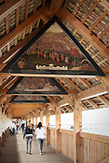 Inside the Chapel Bridge, where painting decorate panels along nearly its entire length. Lucerne, Switzerland.