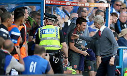 Arsenal manager Arsene Wenger (right) shakes hands with his staff before the final whistle