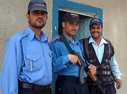Three members of the Iraqi police force pose for photos outside a vehicle checkpoint on one of the roads in the Basra area of Iraq.